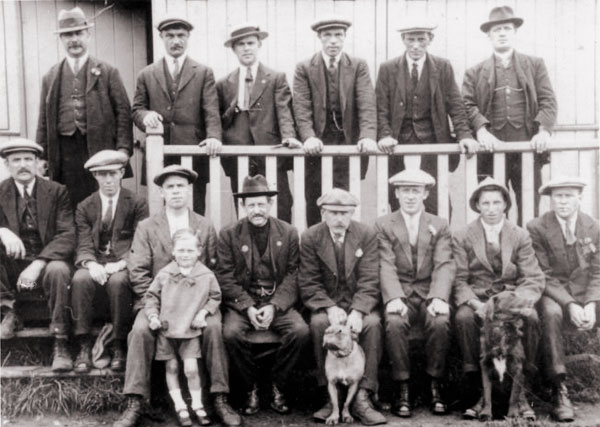 In front of the wooden pavilion just before the First World War. George 'Big Spoff' Charlton is seated at the far left and Wilfrid Hall is seated second from right.