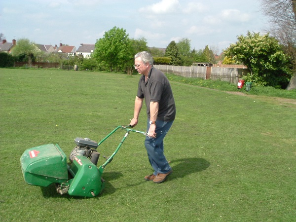 Ian Crisp using the mower to prepare the wicket