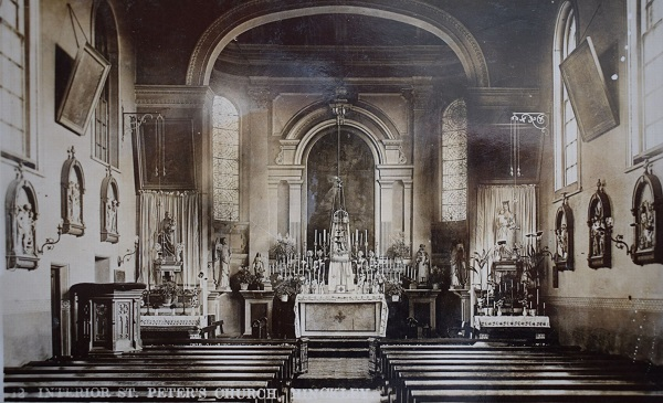 church interior, about 1905, showing the shallow apsidal Renaissance-style sanctuary traditionally dressed and flanked by shrines of Our Lady and St. Peter, with Stations of the Cross and oil paintings adorning the nave walls
