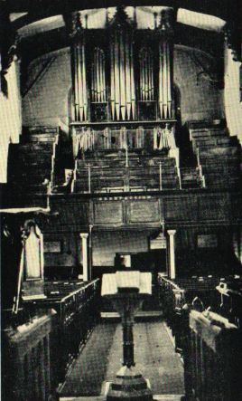 Interior looking west before the restoration, showing the west gallery and organ